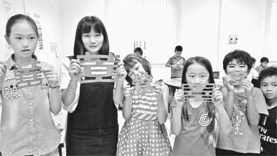 中国志愿者在老挝白云碧国际学校传播中国文化。图为志愿者胡佳佳(左二)和学生们展示他们的剪纸作品。中国青年志愿者赴老挝服务队供图
