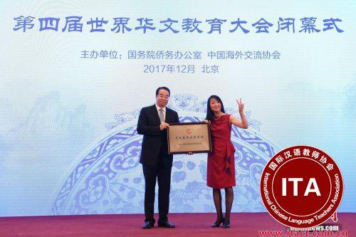 12月20日,第四届世界华文教育大会在北京闭幕。图为国务院侨务办公室党组书记、副主任许又声(左)向法国小熊猫学校校长罗坚海外华文教育示范学校授牌。 <a target=