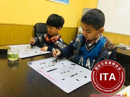 中国侨网西班牙爱华中文学校的学生在练习写书法。(西班牙《欧华报》)