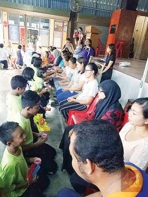 公益华小的各族学生,跪下捧茶给养育他们长大的长辈们。(马来西亚《光华日报》)